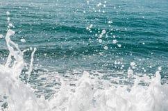 Kraftiga vågor av havet som skummar som bryter mot den steniga kusten texturerat hav Athens Grekland royaltyfri foto