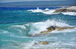 Kraftiga vågor som krossar på en stenig kustlinje Arkivfoton