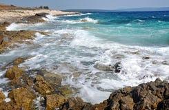 Kraftiga vågor som krossar på en stenig strand Arkivbild