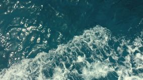 Kraftiga vågor som ut dras från det snabba rörande fartyget, en enorm ström av djupblått vatten med vitt skum som stiger upp som  arkivfilmer
