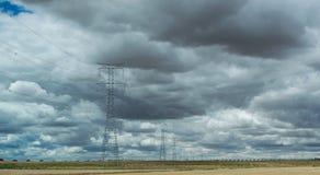 Kraftledning med dramatiska moln i öken Arkivbild