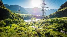 Kraftledningar i de lösa bergen i Altai, Sibirien, Ryssland vid den Katun floden royaltyfri foto