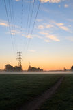 Kraftledningar i morgonsoluppgång arkivbild