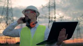 Kraftledningar och en manlig tekniker med en bärbar dator som talar på en telefon nära dem stock video