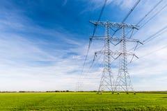 Kraftledningar och pyloner i ett lantligt landskap Arkivbild