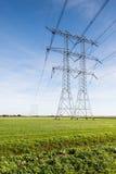 Kraftledningar och pyloner i ett lantligt landskap Arkivfoto