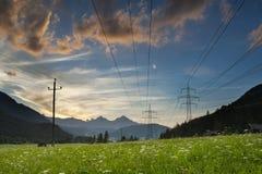 Kraftledningar och pylons på solnedgången Royaltyfria Bilder