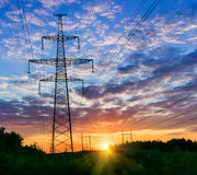 Kraftledningar på en färgrik soluppgång, elkraftlinjer mot himmel på soluppgång Arkivfoton