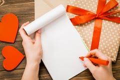 Kraftpapier-document envelop met houten rood hart op houten lijst met Stock Afbeeldingen