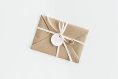 Kraftpapier-envelop met teg met hart en lint op wit wordt geïsoleerd dat Stock Foto