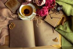Kraftpapieranmerkung mit Tasse Tee, Blumen, Pfingstrosen, alte Weinleseuhr Retro- Hintergrund Modernes Tonen Copyspace für Text,  Lizenzfreies Stockbild