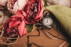 Kraftpapieranmerkung mit Tasse Tee, Blumen, Pfingstrosen, alte Weinleseuhr Retro- Hintergrund Modernes Tonen Copyspace für Text,  Lizenzfreie Stockfotos
