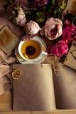 Kraftpapieranmerkung mit Tasse Tee, Blumen, Pfingstrosen, alte Weinleseuhr Retro- Hintergrund Modernes Tonen Copyspace für Text,  Lizenzfreie Stockbilder