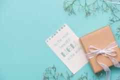 Kraftpapiergeschenkbox gebunden mit weißem Band und Blumen für Motte Stockfotografie