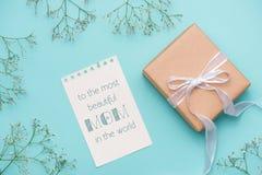 Kraftpapiergeschenkbox gebunden mit weißem Band und Blumen für Motte Lizenzfreie Stockfotos