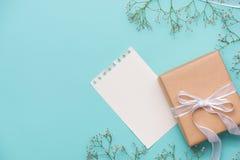 Kraftpapiergeschenkbox gebunden mit weißem Band und Blumen für Motte Stockfoto