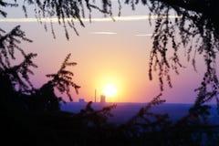 Kraftverk framme av en solnedgång Arkivbild