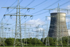 Kraftverk- och elektricitetspyloner mellan träd Arkivfoto