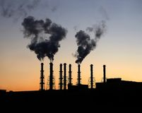 Kraftwerkgebäude mit vielen hohen Schornsteinen nach Sonnenuntergang Stockfotos