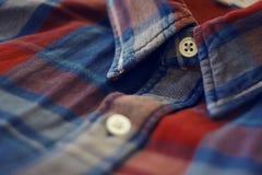 Kragen av den röda och blåa rutiga skjortan som knäppas royaltyfri fotografi