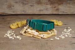 Kragen- und Hundeknochen auf hölzernem Hintergrund es ist Snack für Hund lizenzfreie stockfotos