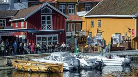 Norwegians rest on the shore of the fjord among traditional architecture, spring and Easter. Kragero, Norway - April 12, 2015: Easter traditions in southern stock photography