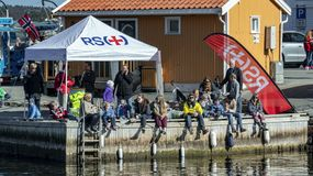 Norwegians rest on the shore of the fjord among traditional architecture, spring and Easter. Kragero, Norway - April 12, 2015: Easter traditions in southern stock images