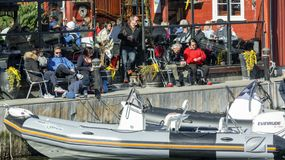 Norwegians rest on the shore of the fjord among traditional architecture, spring and Easter. Kragero, Norway - April 12, 2015: Easter traditions in southern royalty free stock photography
