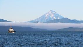 Krai van Rusland, Kamchatka - 31 Augustus, 2018: Het Weergeven van Vilyuchinsky-vulkaan riep ook Vilyuchik van toeristenboot stock afbeelding