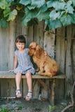 Kraj dziewczyny obsiadanie na ławce z jej psem pod winogradem Drewniany obraz royalty free