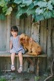 Kraj dziewczyny obsiadanie na ławce z jej psem pod winogradem Drewniany obrazy stock