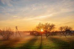 Krajobraz jesień i mgłowy wsi greenfield z wioską na tle przy zmierzchem obrazy stock