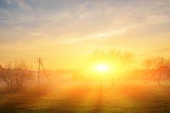 Krajobraz jesień i mgłowy wsi greenfield z wioską na tle przy zmierzchem fotografia royalty free