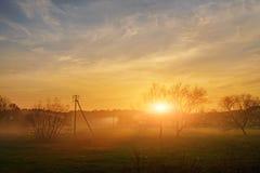 Krajobraz jesień i mgłowy wsi greenfield z wioską na tle przy zmierzchem zdjęcie royalty free
