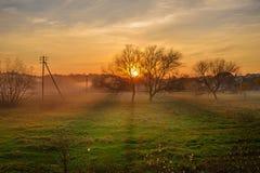 Krajobraz jesień i mgłowy wsi greenfield z wioską na tle przy zmierzchem fotografia stock