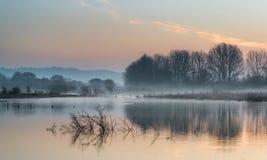 Krajobraz jezioro w mgle z słońce łuną przy wschodem słońca Obrazy Royalty Free
