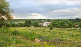 Krajobraz mali domy na zielonej łące. Zdjęcie Stock