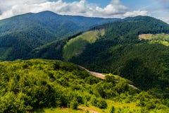 Krajobraz przedstawia doliny, wydrążenia i wspinaczki na ogromnym zielonym pasmie górskim, zdjęcie stock