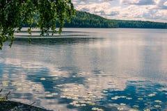 Krajobraz spokojny błękitny jezioro, zielony las i chmurny niebo, fotografia stock