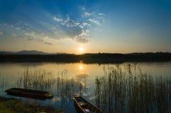 Krajobraz z łódkowatym i dramatycznym zmierzchem z zwartymi trawami Obraz Stock