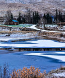 Krajobraz z domem i zamarzniętym jeziorem z białym cisnei zdjęcia stock
