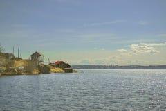 Krajobraz z jeziorem i kilka wioska domami na małym przylądku zdjęcia stock