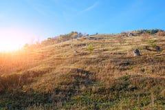 Krajobraz z niebieskim niebem, jesieni muśnięcie na obszarów trawiastych wzgórza i drzewa i Obraz Stock
