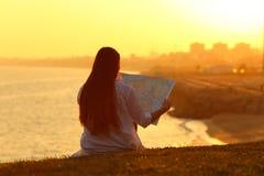 Krajobraz z turystycznym czytaniem mapa przy zmierzchem zdjęcia royalty free