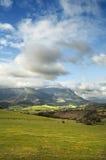 Krajobraz z zielonymi polami, górami i chmurami Obrazy Royalty Free