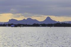 Krajobrazowa fotografia wioska rybacka z górą w zmierzchu Obrazy Royalty Free