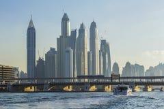 Krajobrazowa motorowa łódź przechodzi pod bridżowymi pobliskimi drapaczami chmur Dubaj Zdjęcia Stock