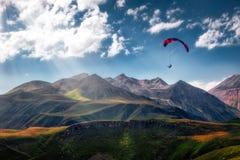 Krajobrazowy widok lata nad pięknymi górami i niebem paraglider fotografia royalty free
