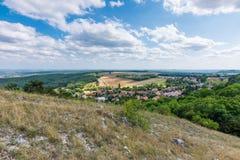 Krajobrazowy widok mała wioska, łąka i rolnictwo, Las na prawej stronie z zielonymi drzewami, niebieskie niebo, chmurnieje obrazy stock
