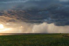 krajobrazu wiejskiego Burz chmury nad jeziorem przy zmierzchem Zieleni ??ki i pola z?oty zmierzch zdjęcie stock